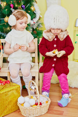 Two little girls sit on wooden chairs in room