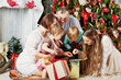 Family of five all together looks into gift box