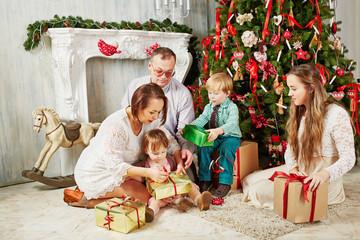 Parents and children sit on rug near Christmas tree