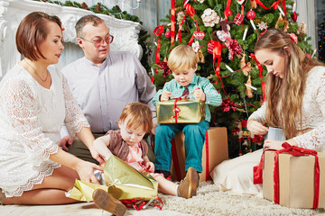 Family of five sits under Christmas tree, parents look at their