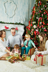 Parents and three their children sit under Christmas tree