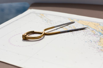 Pair of compasses for navigation on a sea map