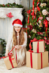 Teenage girl in santa cap sits on furry rug under Christmas tree