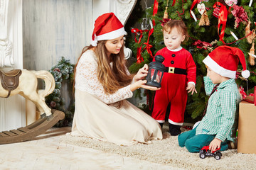 Three children sit on furry rug under Christmas tree