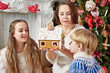 Mother holds gingerbread house, daughter and son look at it