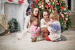 Mother and three children sits under Christmas tree