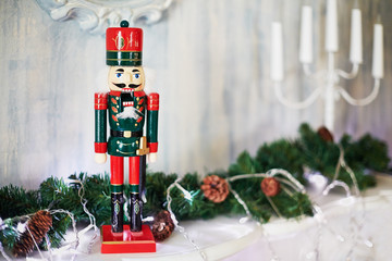 Toy Nutcracker, fir branches with cones and candlestick