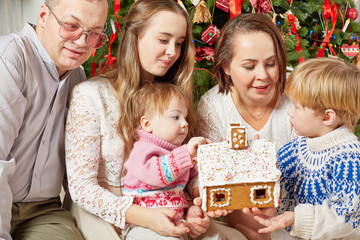 Family of five gathered under Christmas tree around gingerbread