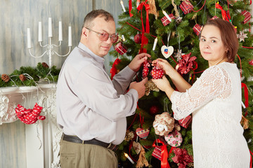 Family decorates Christmas tree with various decorations