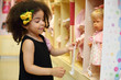 Little smiling girl touches dummy of toy doll in children store.
