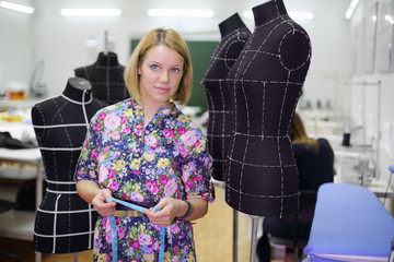 Female tailor stands among four black mannequins and holds tape.