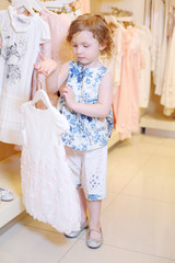 Little girl considers white dress in store with children clothes