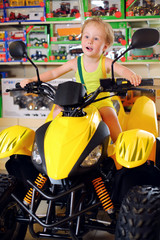 Little cute boy in yellow sits on toy quad bike in store
