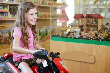 Little cute girl in sits on red toy motorcycle in store with toy