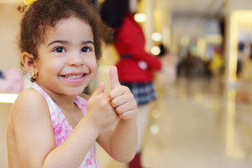Little pretty girl smiles and thumbs up in children store