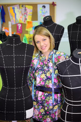 Happy female tailor stands among five black mannequins
