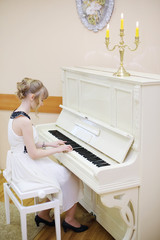 Beautiful girl in white dress plays white piano in light room.