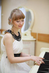 Beautiful smiling girl in white dress plays white piano