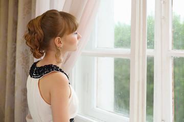 Beautiful sad girl in white dress looks in window in light room.