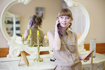 Beautiful girl in modern clothes talks by phone in room