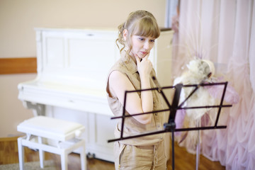 Beautiful girl stands near music stand in room