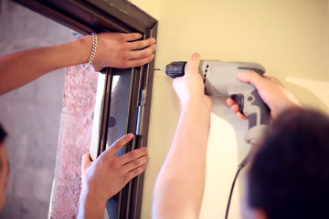 Hands of builders with drill inserting door frame to aperture