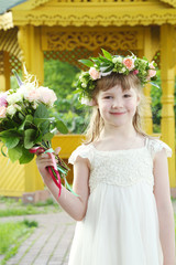 Little girl in white dress and wreath holds bouquet