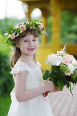 Little pretty girl in white dress and wreath holds bouquet