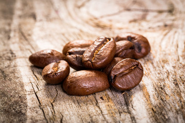 Coffee grains on wooden background.