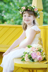 Little pretty girl in white dress and wreath sits