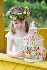 Little pretty girl in white dress and wreath plays with cage