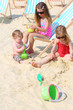 Three happy children sit on beach and play with toys