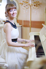 Beautiful girl in white dress plays white piano and looks