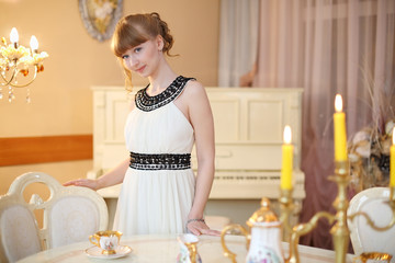 Pretty girl stands next to classic white table with dishes