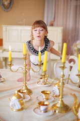 Pretty girl stands near white table with dishes