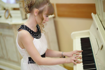 Beautiful focused girl in white dress plays white piano