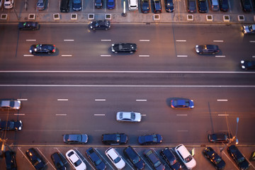Top view of wide road with markings and lots of cars at night.