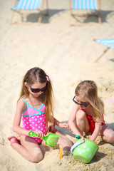 Two happy little girls sit on beach and play with sand at sunny