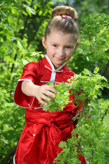 Little girl in red kimono for karate is among greenery