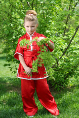 Little sad girl in red kimono for karate is among greenery