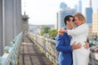 Pregnant woman in white and stylish man embrace outdoor