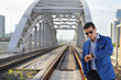 Handsome man in blue jacket and sunglasses stands on railroad