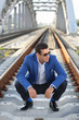 Handsome man in blue jacket and sunglasses squats on railroad