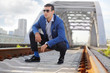Stylish man in blue jacket and sunglasses squats on railroad