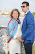 Stylish man in jacket and pregnant woman stand on bridge