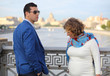 Stylish man in blue jacket and pregnant woman stand on bridge
