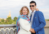 Stylish man in blue jacket and pregnant woman smile