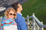 Stylish man in blue jacket and woman in sunglasses stands