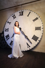 brunette woman in white dress stands near big clock