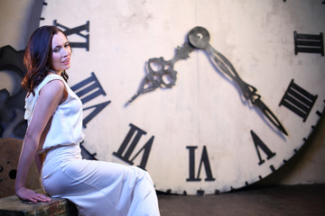 brunette woman in white dress sits near big clock